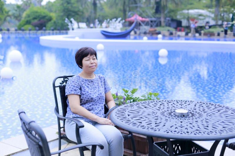 Kinesiskt medelålderst kvinnasammanträde på en stol bredvid pölen arkivfoto