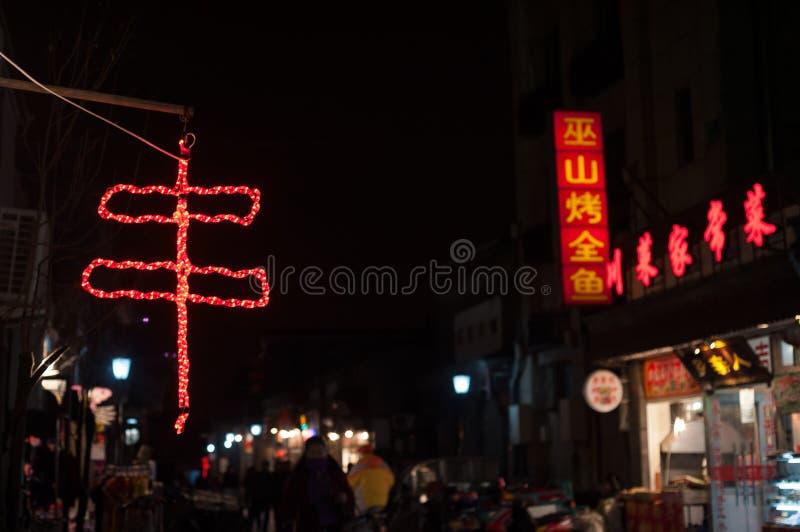Kinesiskt symbol för chuan för kebab som visas som ett rött neontecken utanför en restaurang i en Pekinggata royaltyfri foto