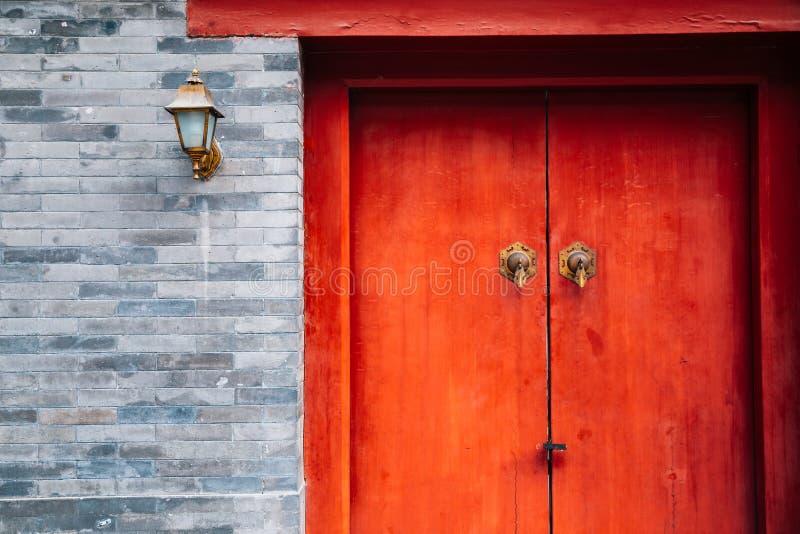 Kinesiskt traditionellt hus, gammal tegelstenvägg och röd dörr arkivfoto