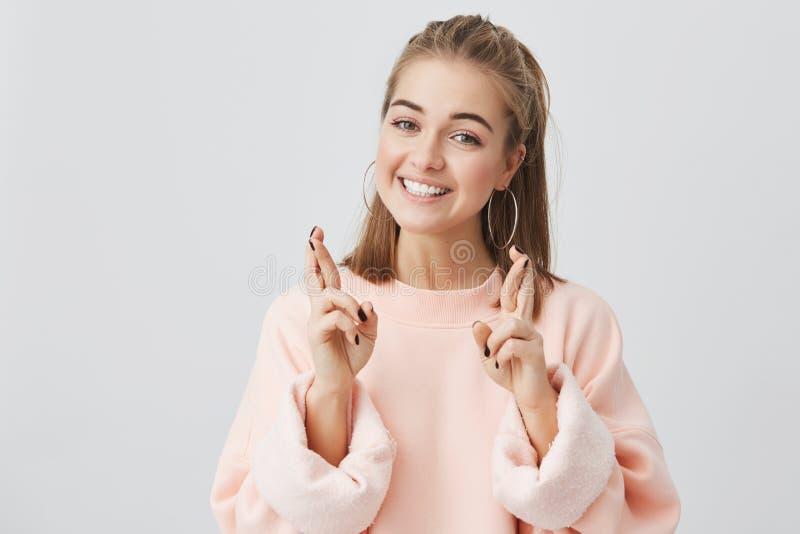 Kinetisch gedrag Bijgelovig tienermeisje met blondehaar en mooi gezicht die vingers voor goed geluk kruisen, die haar hopen stock fotografie