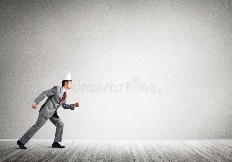 King businessman in elegant suit running in empty room stock photos