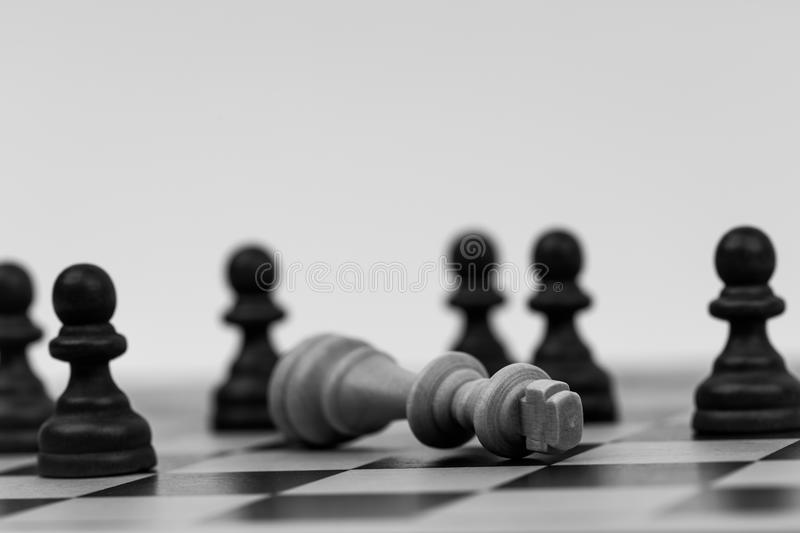 King in chess has fallen to several pawns stock photo