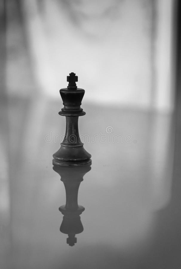 King Chess Piece in Monochrome. Single classical wooden king chess piece in black and white with shadow areas and reflections from a glass surface. Vertical royalty free stock photos