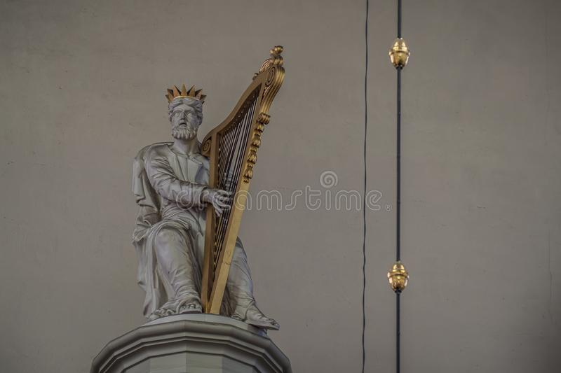 King David with harp on top of the Batz organ in the Dom Church in Utrecht. Utrecht, Netherlands - August 13, 2016: Wood carved figure of king David with harp on stock photography