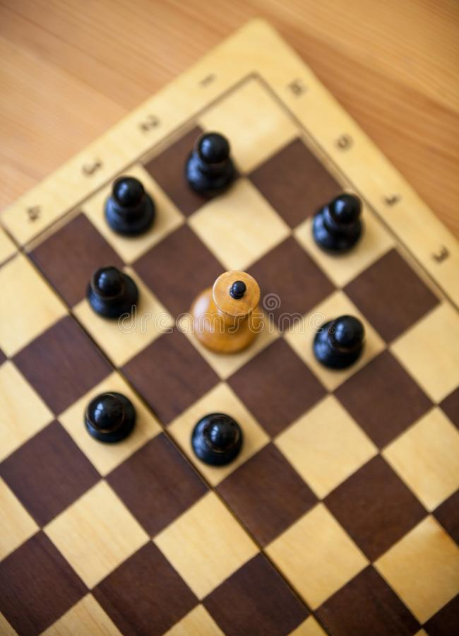 King encircled by the pawns. Chess pieces. White king encircled by the black pawns. Wooden chess pieces on the chessboard. Chess game. Top view stock photography