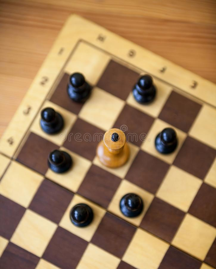 King encircled by the pawns. Chess pieces. White king encircled by the black pawns. Wooden chess pieces on the chessboard. Chess game. Top view royalty free stock photo