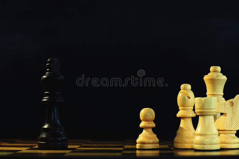 King encounters against powerful pawn in chess game, business competitive concept. Copy space royalty free stock photos