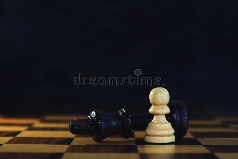King encounters against powerful pawn in chess game, business competitive concept. Copy space royalty free stock images