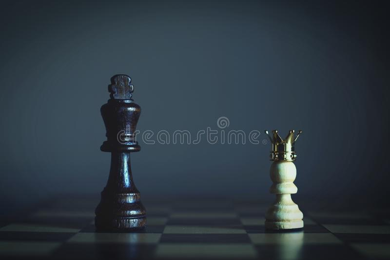 King encounters against powerful pawn with gold crown, business competitive concept, copy space. King encounters against powerful pawn with gold crown, business royalty free stock images
