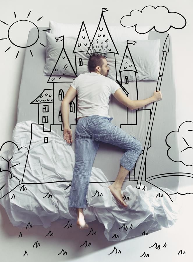 Top view photo of young man sleeping in a big white bed and his dreams royalty free stock image