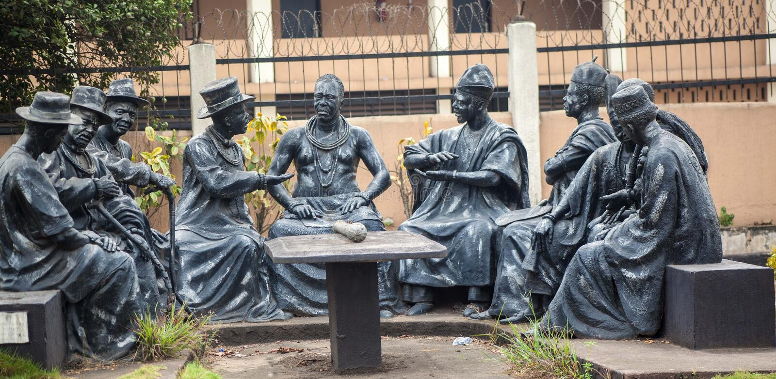 The King with his Elders. Statues of several men gathered around a table. They seem to be chiefs advising a king royalty free stock photo