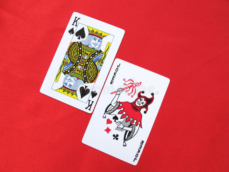 King and Joker. King of spades and joker isolated on red background stock photo
