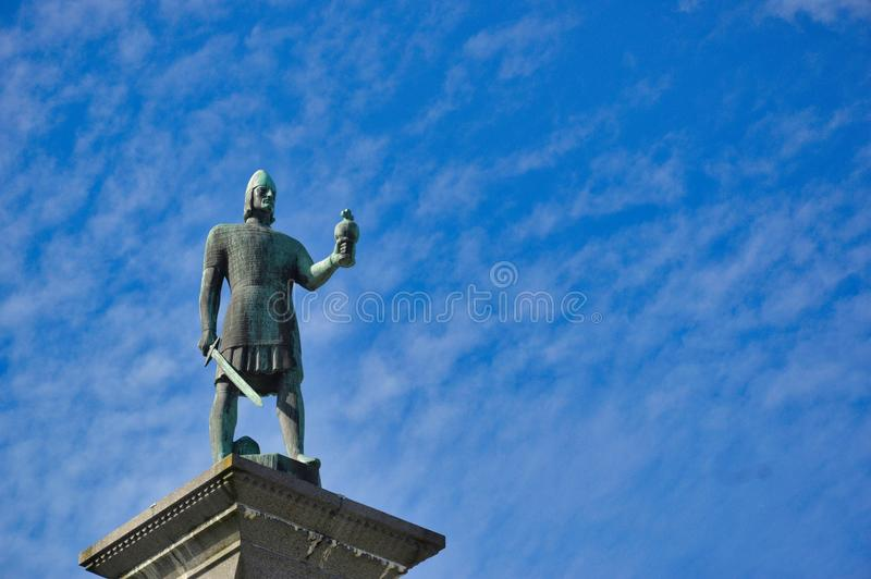 King Olav statue in Trondheim, Norway. King Olav statue downtown Trondheim, with spectacular blue, white-stripped, sky background stock images