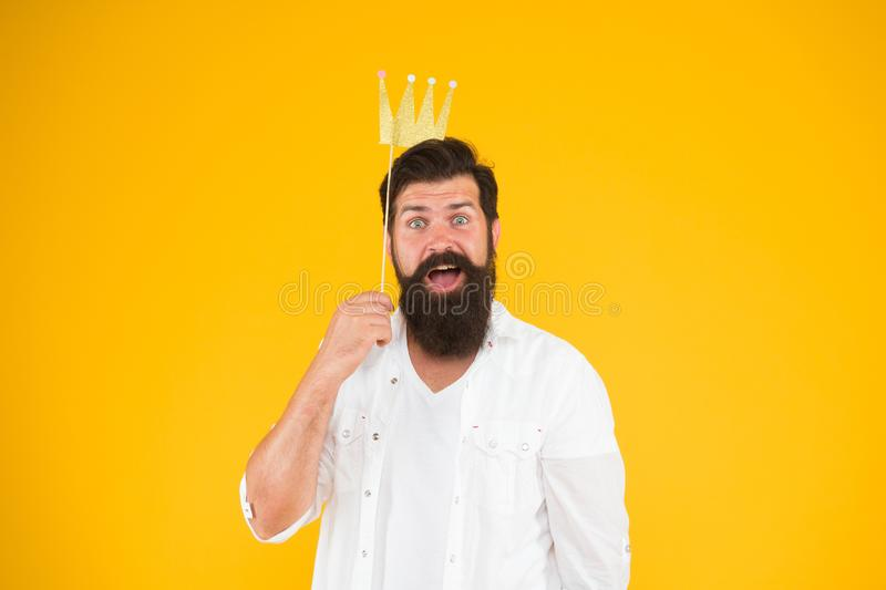 King of party. Costume party. Holiday carnival celebration. Birthday boy. Handsome bearded guy king. Guy in yellow. Background posing with booth props. Photo stock image