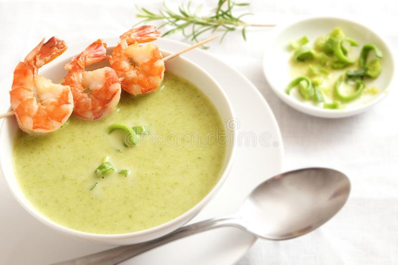 King prawn skewer on green vegetable cream soup, white tableware stock photos