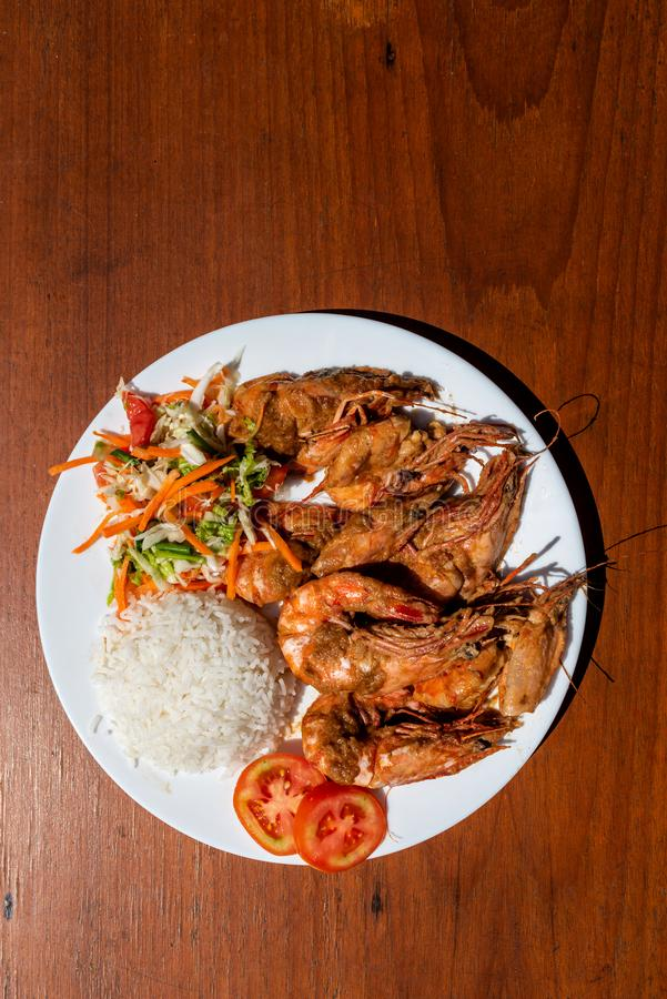 King prawns with side dish and salad on a wooden table. Top view. stock photography