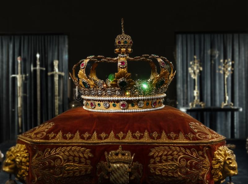 King`s gold crown. Gold and jewell-studded King`s crown on a ceremonial pillow royalty free stock photos