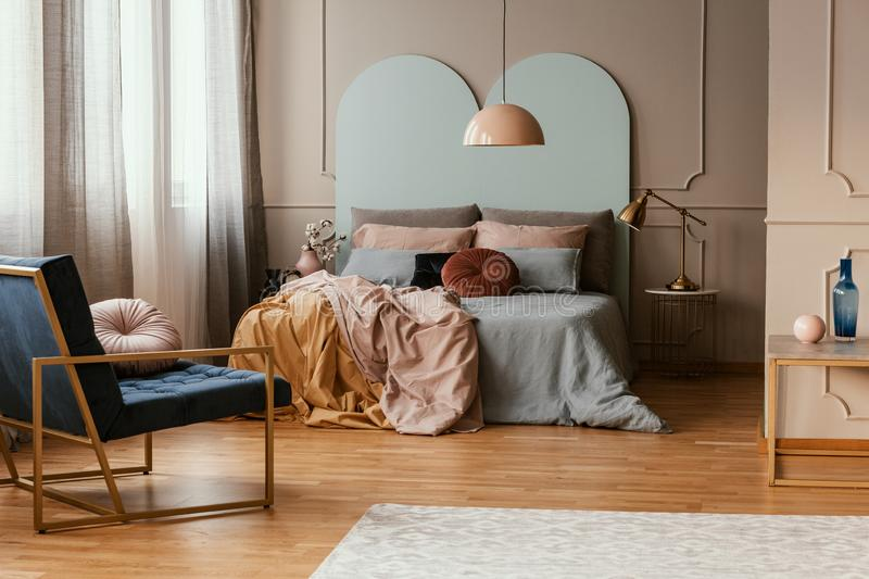 King size bed with pastel colored bedding in classy bedroom. King size bed with pastel colored bedding in bedroom royalty free stock image