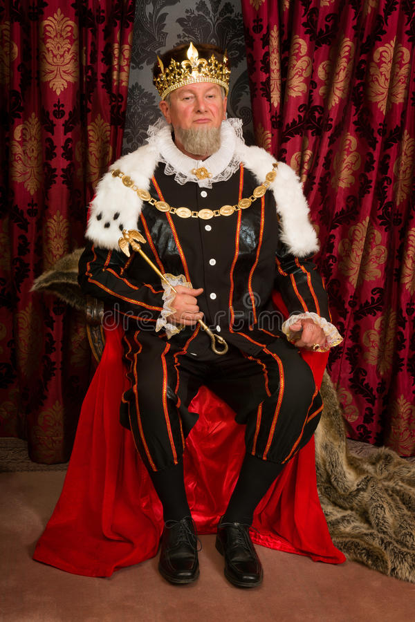 King on throne. King in tudor costume sitting on his throne holding his scepter stock photography