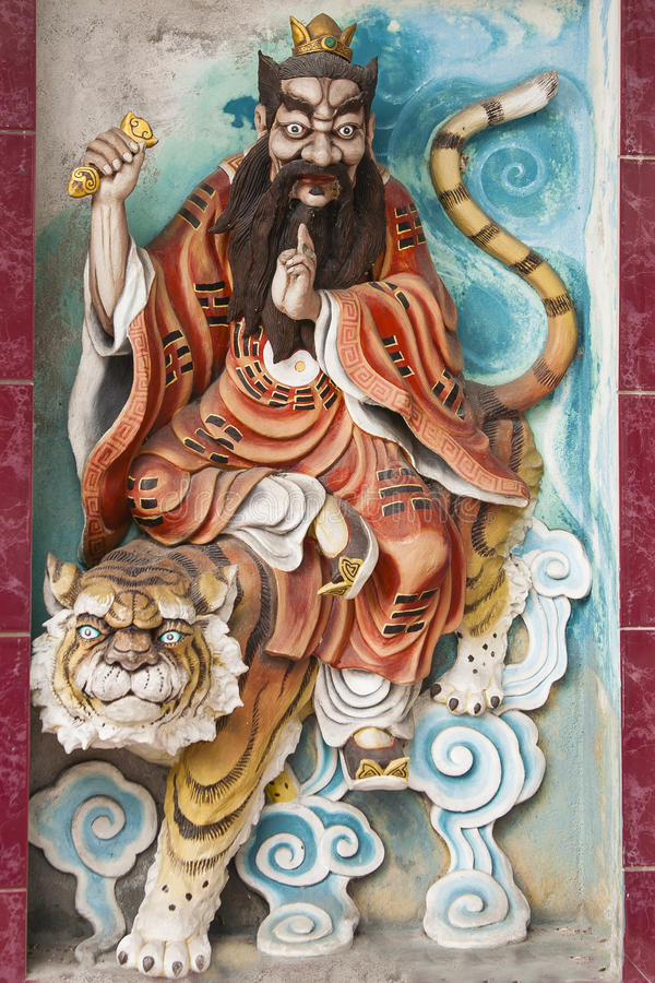 King on Tiger Bas Relief. Bas relief sculpture of a king with crown and long beard in a colorful orange robe riding on a tiger on blue clouds, side of a temple royalty free stock photos