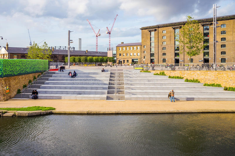 Kings cross London canal. LONDON - OCTOBER 17: People sitting by the canal in Kings Cross outside the Central Saint Martins university campus. Tourists and royalty free stock image