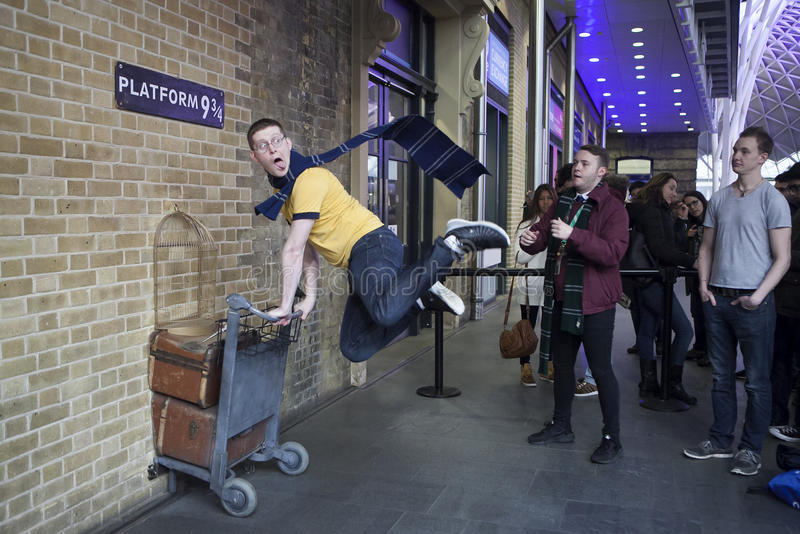 Kings Cross station wall visited by fans of Harry Potter to photograph sign for platform nine and three quarters with trolley. LONDON, UK - MAR 19, 2016: Kings royalty free stock image