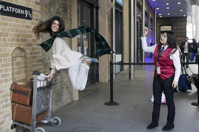 Kings Cross station wall visited by fans of Harry Potter to photograph sign for platform nine and three quarters with trolle stock photos