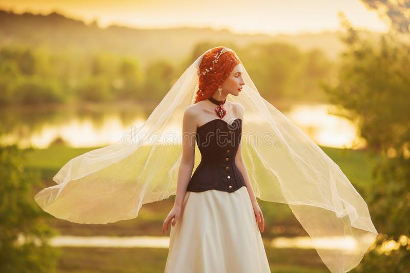 Kinky renaissance princess on veil on nature background. Velvet necklace. Rococo queen in corset against backdrop of sunset. Kinky. Princess in veil stock photography