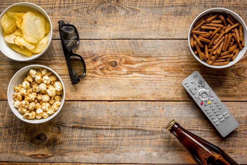 Kino i TV whatching z piwa, kruszek, układów scalonych i wystrzał kukurudzy tła odgórnego widoku drewnianym egzaminem próbnym, obraz royalty free