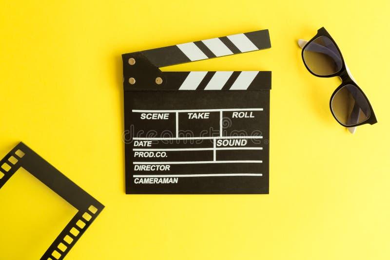 Kino und Film, die Hintergrund machen Clapperboard mit Gläsern 3d und Rahmen in der Form des Filmstreifens lokalisiert auf gelbem stockbilder