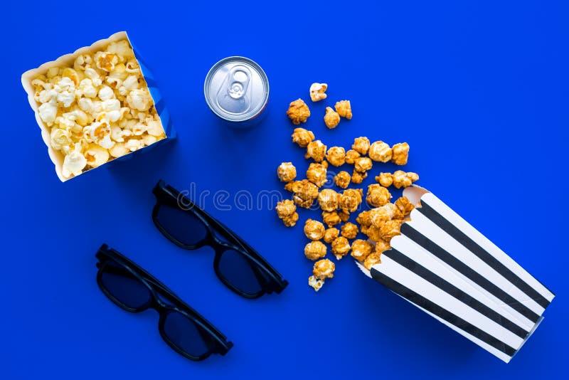 Kinowe przekąski Popkorn w papierowej torbie i miękkim napoju blisko szkieł na błękitnej tło odgórnego widoku kopii przestrzeni zdjęcie stock