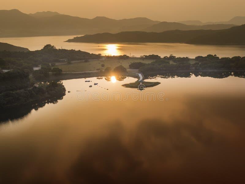 Kiosk för kinesisk stil bredvid en sjö i solnedgång arkivbild