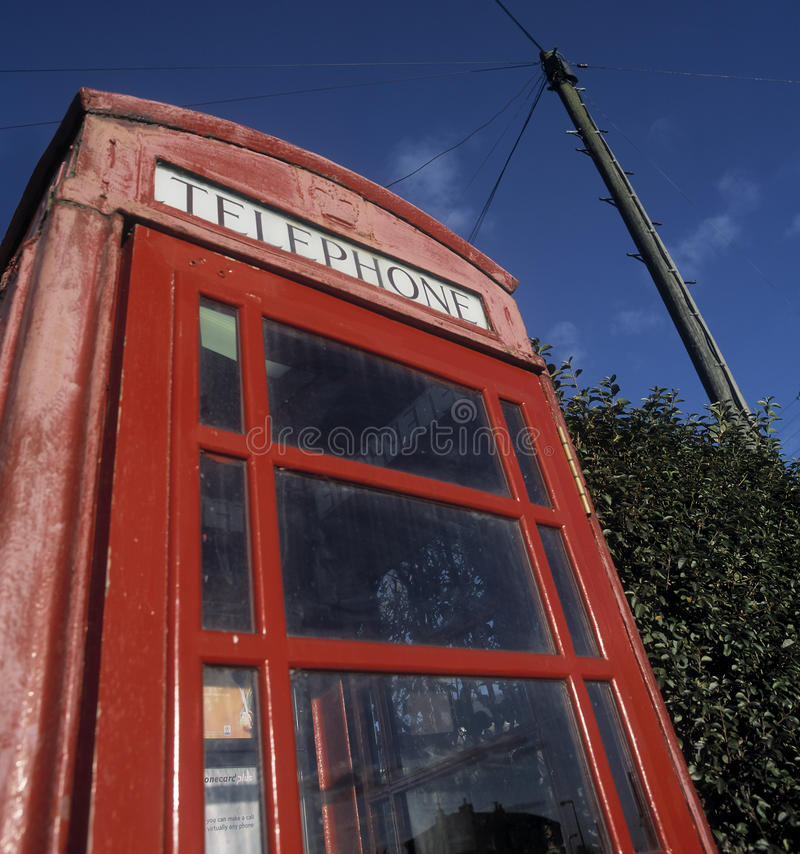 Kiosque de téléphone rouge traditionnel avec le poteau de télégraphe à l'arrière-plan image libre de droits
