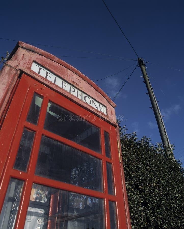 Kiosque de téléphone rouge traditionnel avec le poteau de télégraphe à l'arrière-plan photo libre de droits