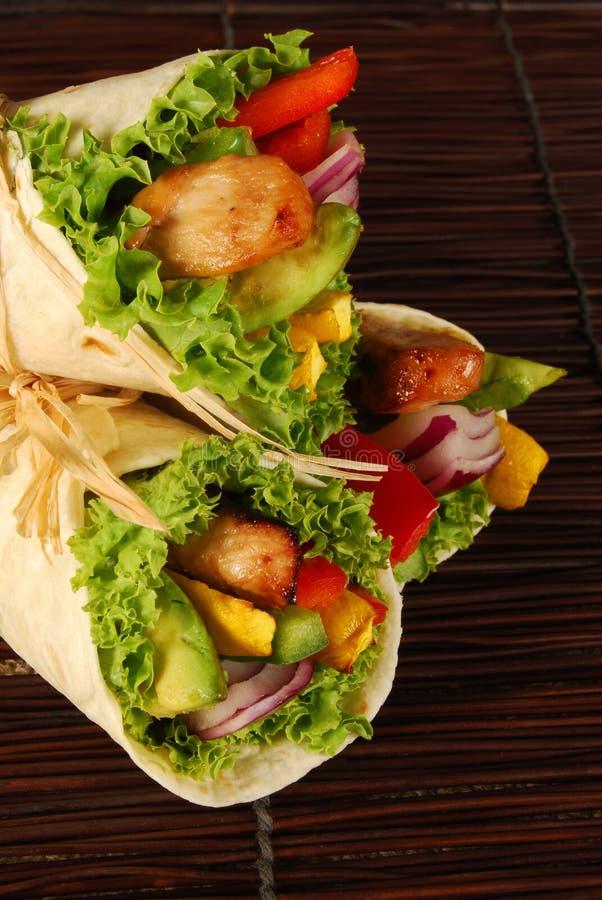 Kip en avocadoomslagsandwiches op mat stock afbeelding