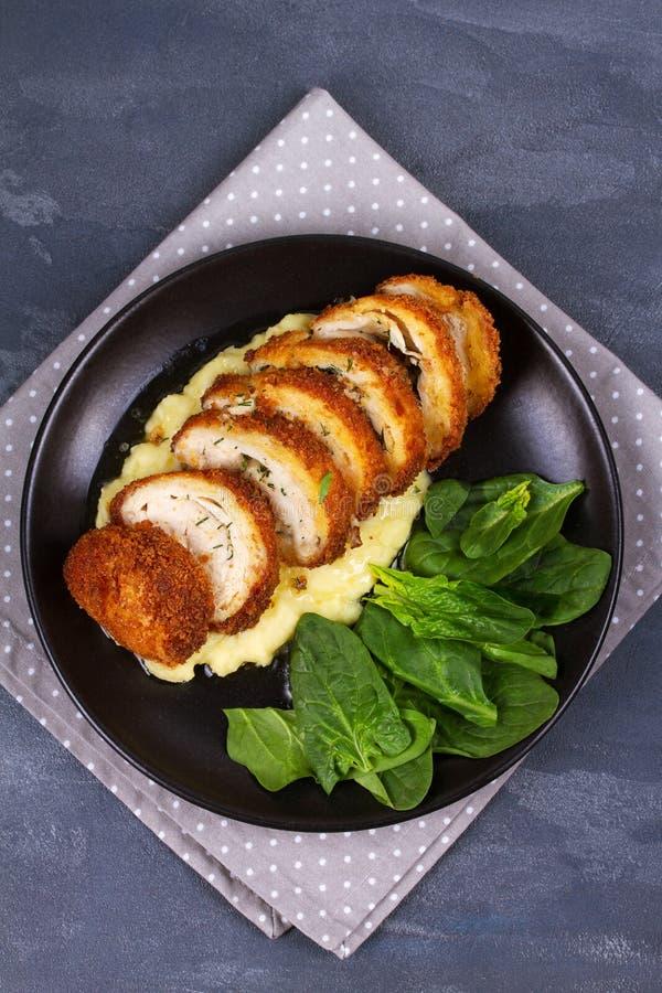 Kip Kiev op fijngestampte aardappel met spinazie Gepaneerde die kippenborst met kruiden en boter wordt gevuld royalty-vrije stock foto