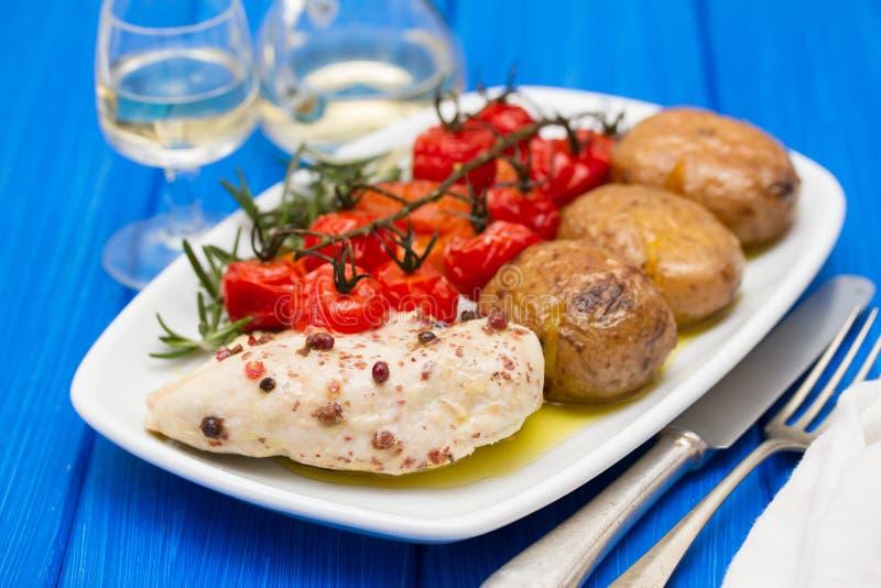 Kip met aardappel en tomaat stock foto's