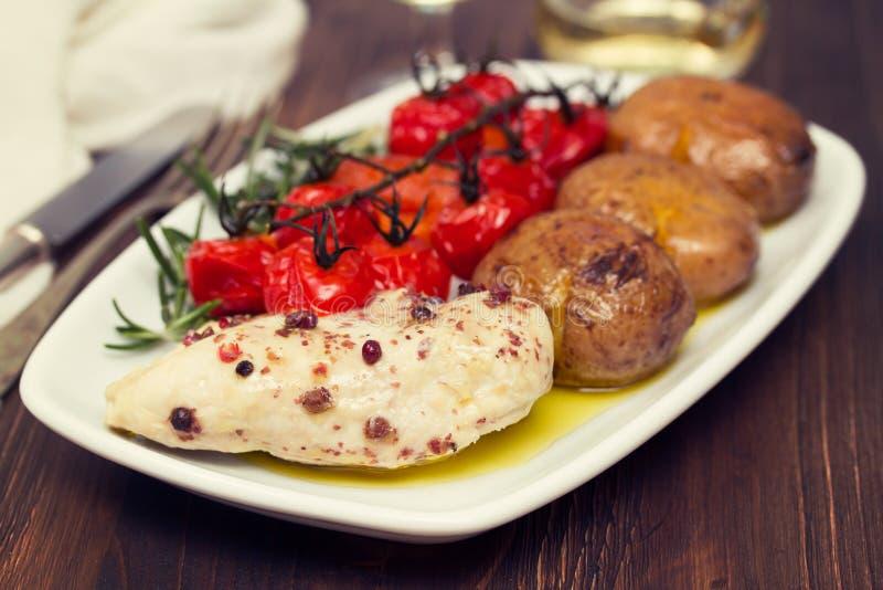 Kip met aardappel en tomaat stock afbeeldingen
