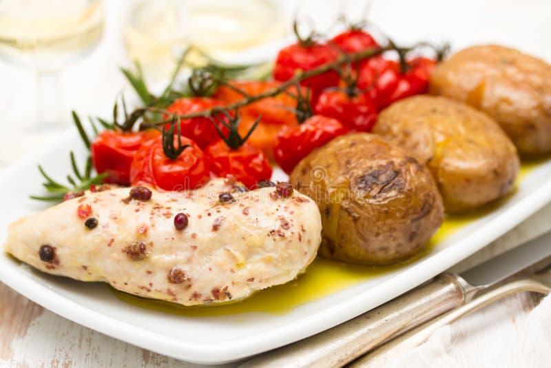 Kip met aardappel en tomaat op schotel stock foto