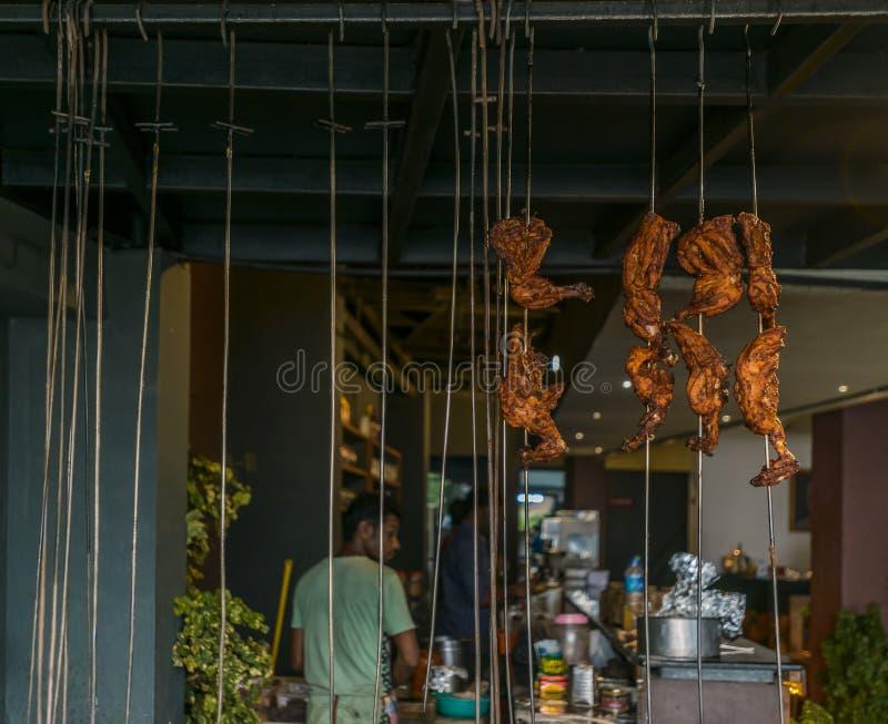 Kippenbenen die op vleespennen in een Indisch restaurant hangen stock foto's