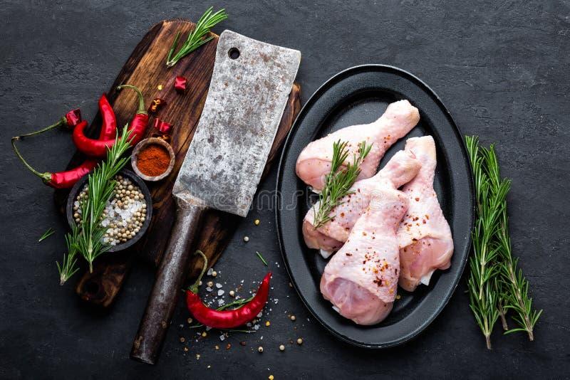 Kippenbenen, trommelstokken en ingrediënten voor het koken, ruw vlees op zwarte achtergrond stock foto's