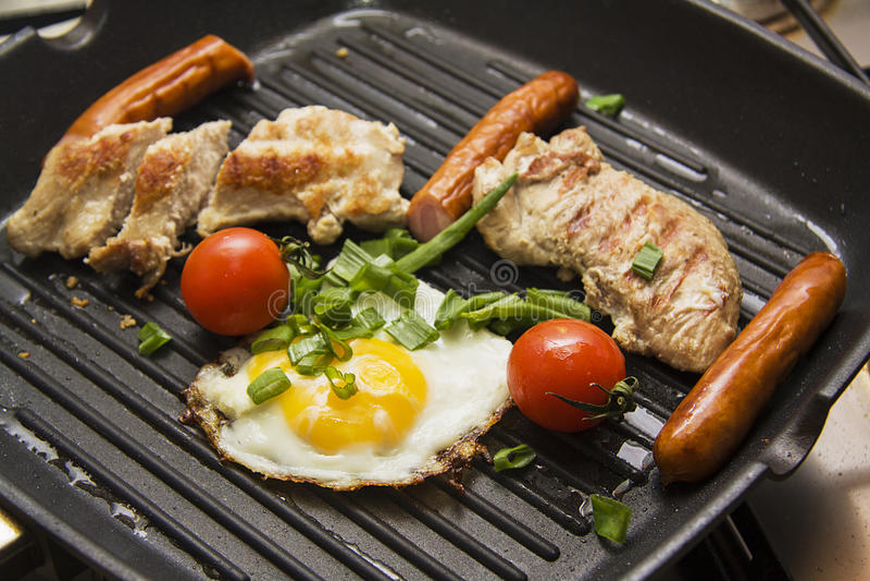 Kippenborst bij de grill met ei, worsten en twee tomaten royalty-vrije stock foto
