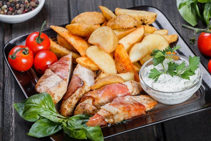 Kippenborst in prosciuttovlees wordt verpakt met geroosterde aardappel, saus, tomaten en greens op donkere houten achtergrond die royalty-vrije stock afbeeldingen