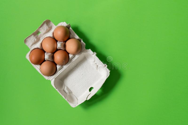 Kippeneieren in ecologische document verpakking op een groene achtergrond stock afbeelding