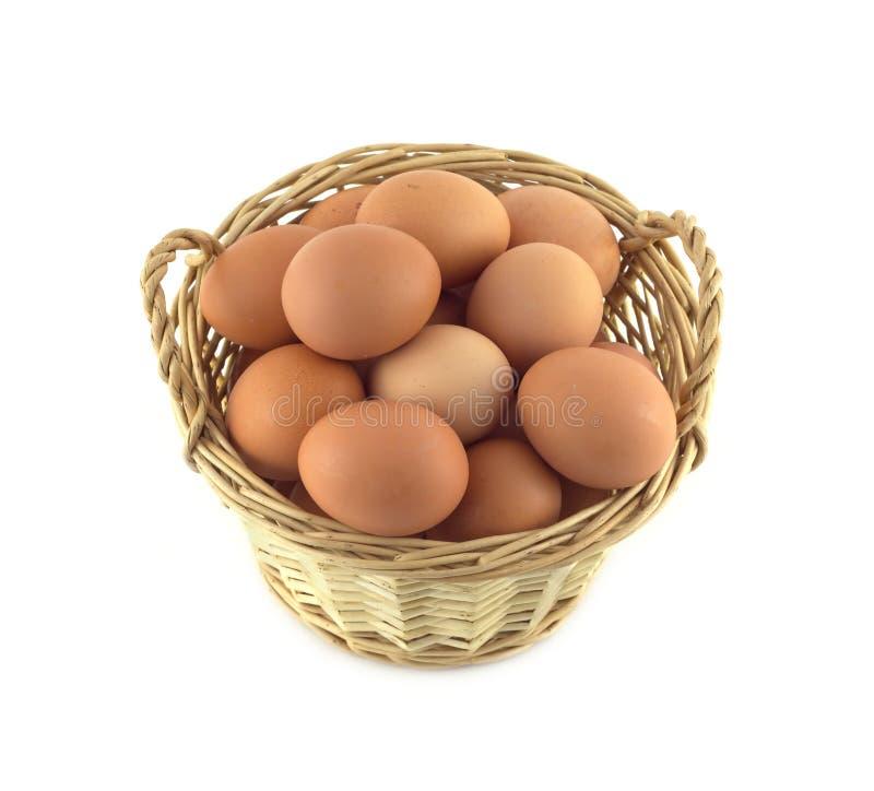 Kippeneieren in rieten mand die op witte close-up wordt geïsoleerd stock foto