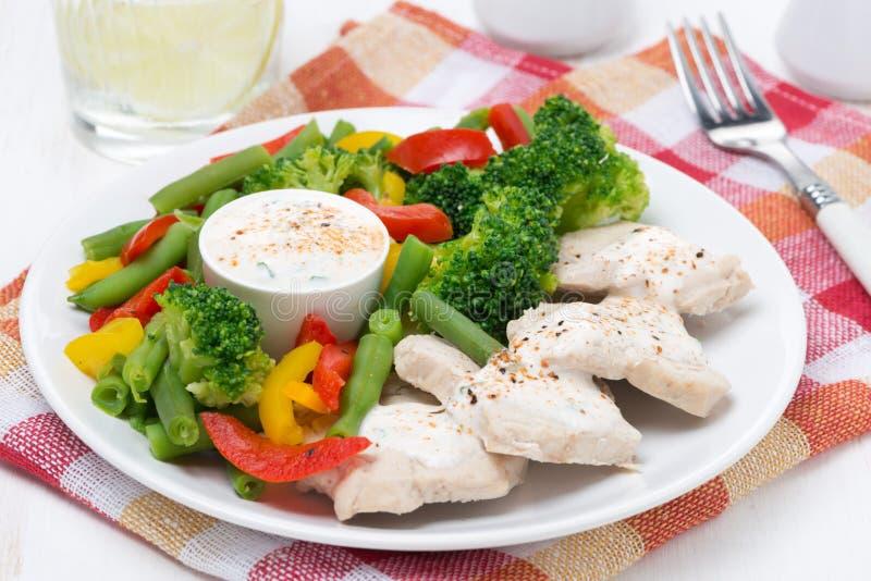 Kippenfilet, gestoomde groenten en yoghurtsaus op een plaat stock foto