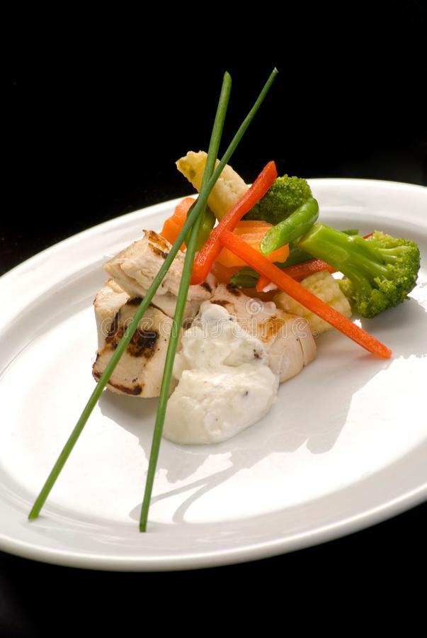 kippenfilet, gestoomde groenten en yoghurtsaus op een plaat, close-up stock foto