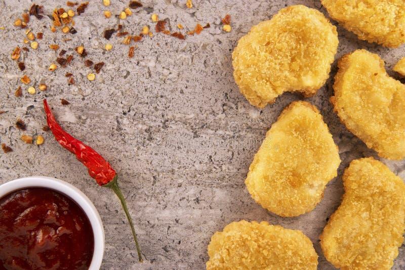 Kippengoudklompjes met een roodgloeiende Spaanse peperpeper en een kom saus royalty-vrije stock foto's