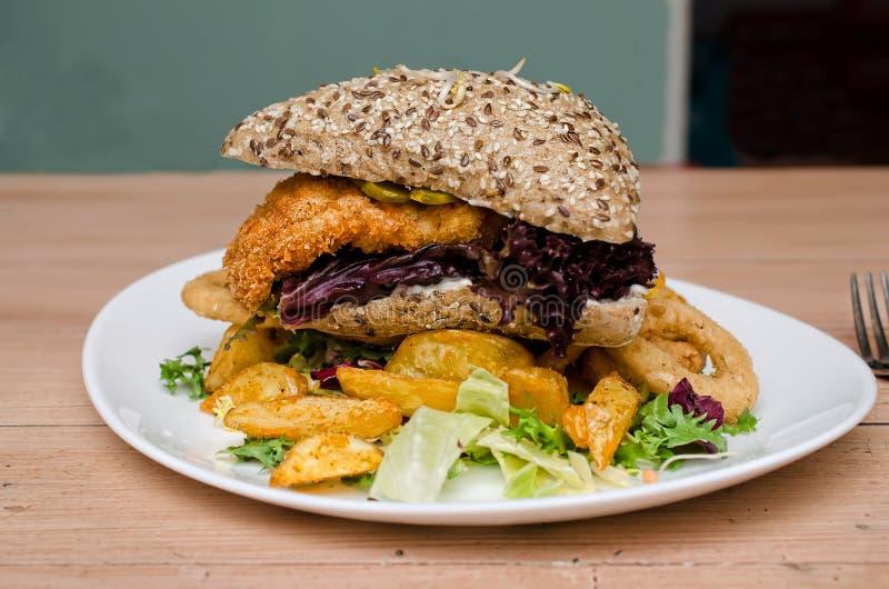Kippenhamburger met gebraden gerechten en uiringen royalty-vrije stock foto's