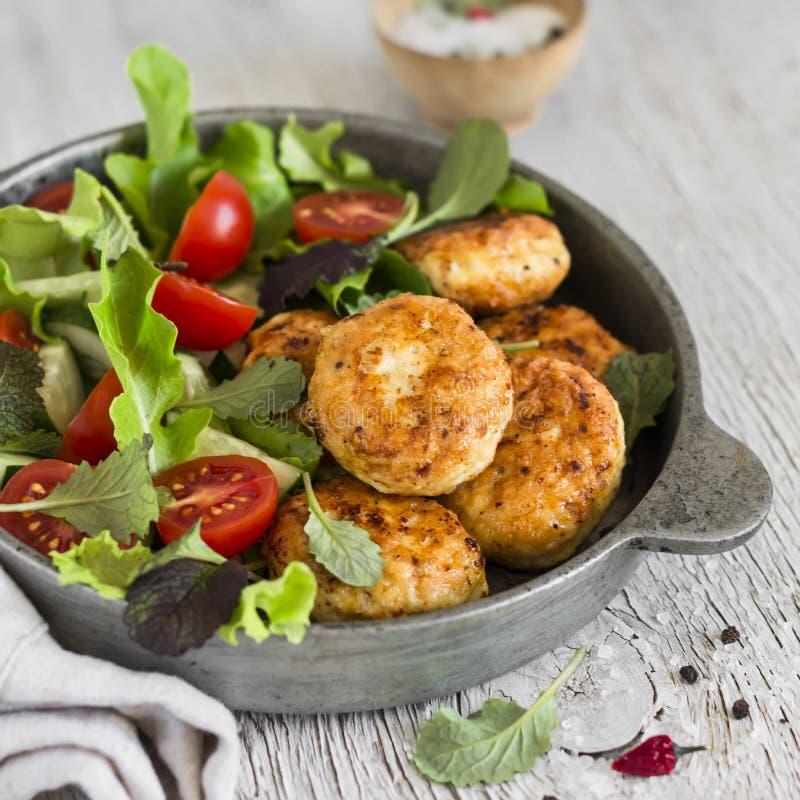 Kippenkoteletten en verse groentesalade in een uitstekende pan royalty-vrije stock afbeeldingen